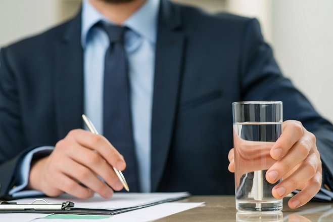 Pleasant office worker holding glass of water